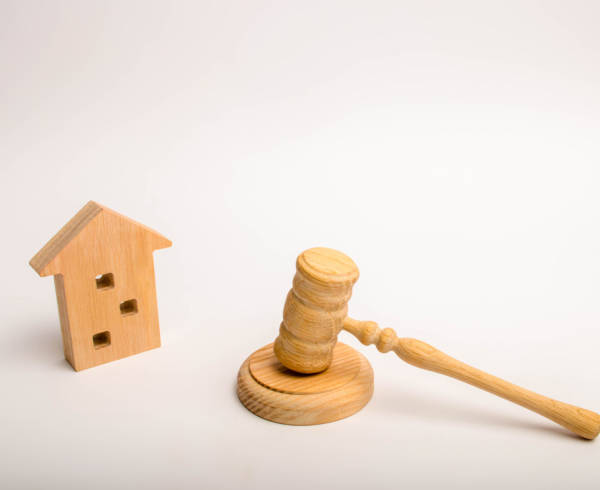 A wooden house and a hammer of the judge. Permission for construction. Court cases on residential buildings. Conflict between neighbors. Demolition of old housing for the construction of a new one.